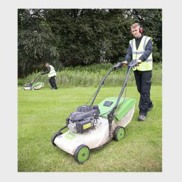 Two people cutting the grass using push lawnmowers