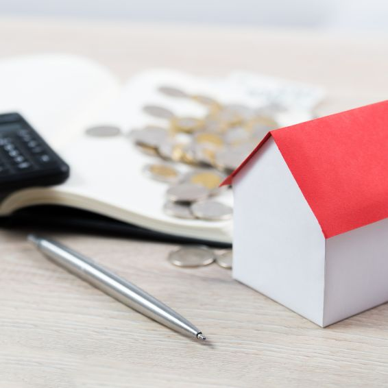 Open notebook with calculator and coins on top next to house-shaped block and a pen